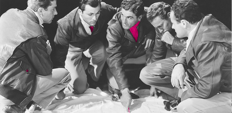 A group of men huddled round a plan, confused. Retro black and white image.