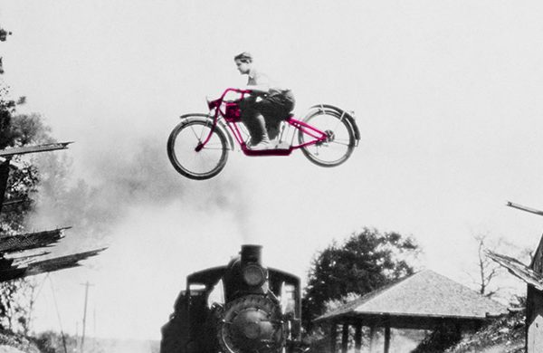 Bike jumping over a ramp, train. Retro black and white image.